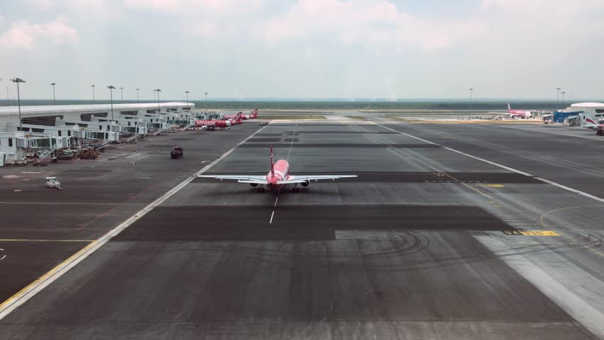 KUALA LUMPUR - MARCH 15, 2017: Air Asia airplane moving to runaway to depart from Kuala Lumpur International 2 Airport.  #27673513