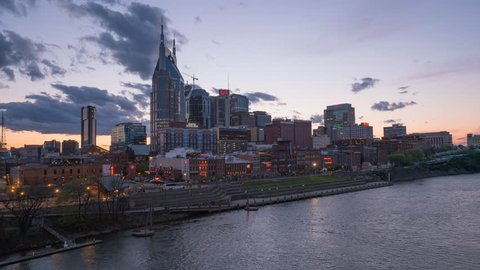 a sunset timelapse of the city of nashville from a bridge across the cumberland river in tennessee