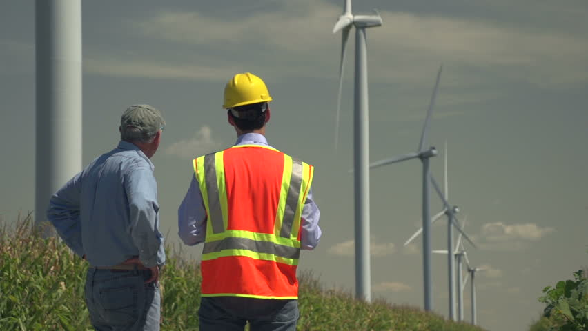 Farmer and engineer looking at windmills, cornfields