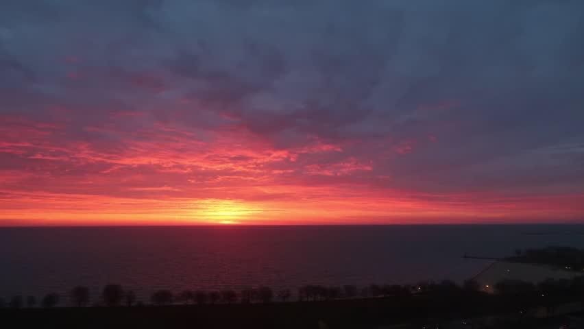 Sunrise time lapse in Chicago over Lake Michigan with white fluffy clouds moving across the sky and bright pink and yellow colors reflecting across the sky and water