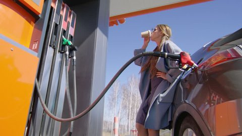 Stylish lady in sunglasses drinking coffee while filling up car tank at gas station at sunny day