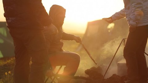 Group of people next to campfire at sunset. Silhouette of peoples cooking and talking in beautiful sunset light with camping on the background.