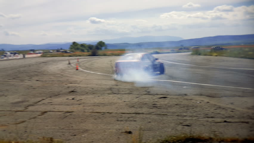 Slow motion of a racing car drifting the turn during a race