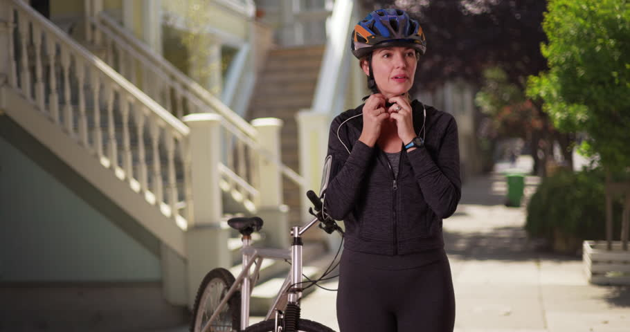 Middle aged Caucasian woman in athletic wear, standing with bike in downtown neighborhood. White female removing helmet after workout with bicycle in daytime. 4k | Shutterstock HD Video #27757579