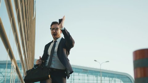 Businessman doing crazy, funny moves while standing outdoors near office building. Business man dancing, doing ninja hands moves. close up