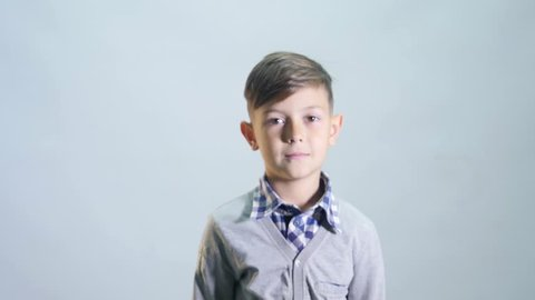 The boy ruffles his hair on grey background.