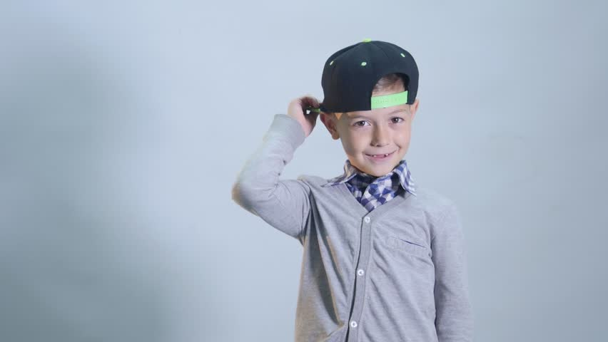 Little boy with toothless smile is wearing a cap.
