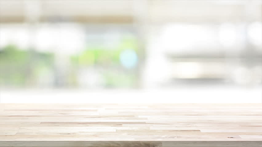 Wood table top on blur kitchen window background - can be used for display your products (or foods)