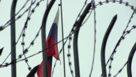 The Barbed Wire on the Sky Background and the Flag of Russia on the Windy Day on. The Concept of Violation of Human Rights in Russia during the Protest Action. Censorship in Russian Mass Media Tools