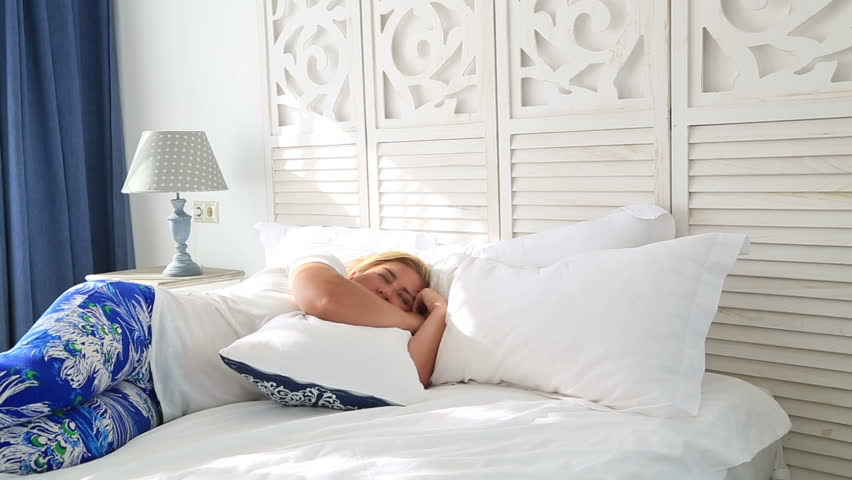 sleeping woman wake up in the morning and yawning with a stretch while sitting in bed