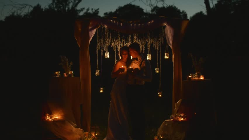 Happy Couple Of Newlyweds Holding Candles In Hands And Looking Each Other The Eye With