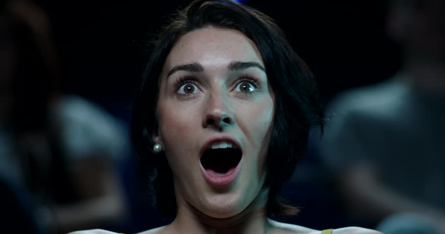 A terrified young woman watches a horror film at the cinema