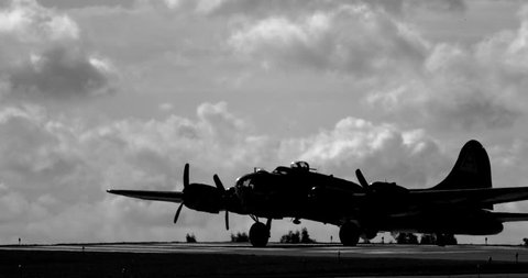 WWII B17 Flying Fortress airplane taxiing on runway in back and white