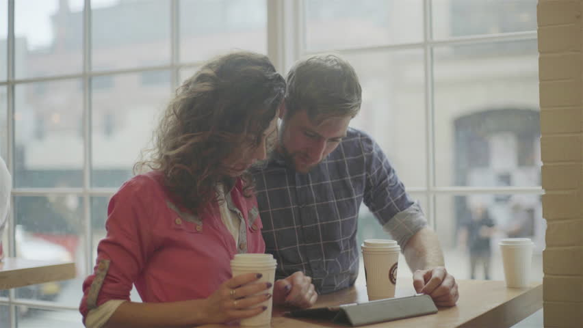 Couple using digital tablet together in coffee shop #27867379