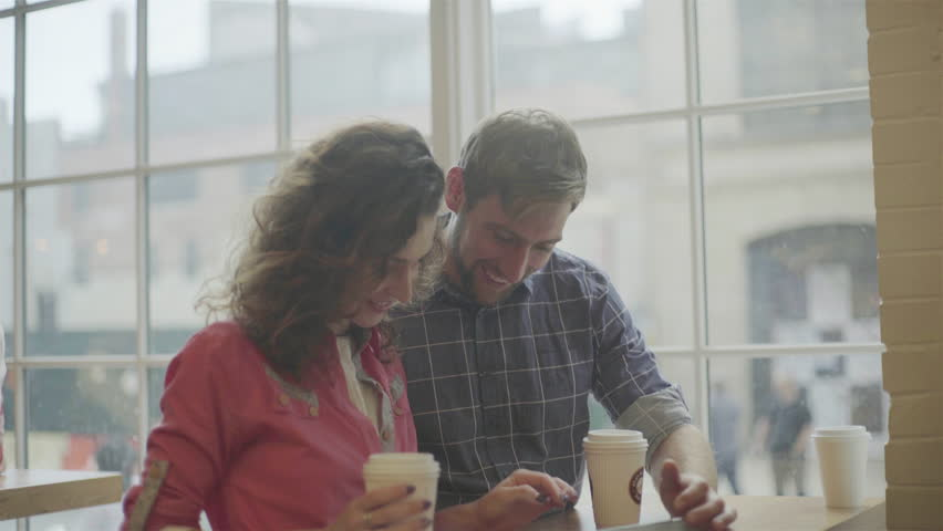 Couple using digital tablet together in coffee shop #27867409