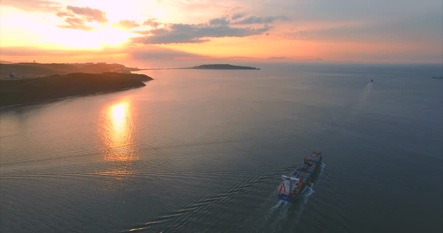 Aerial shot of container ship leaving Vladivostok bay in the morning sunrise.