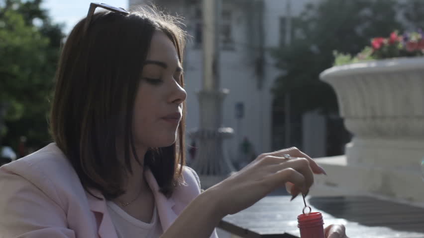 Young pretty girl blows bubbles, outdoor | Shutterstock HD Video #27899359