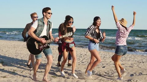 Hipster friends walking and dancing together playing guitar and singing songs on a beach at the water's edge. Slowmotion shot
