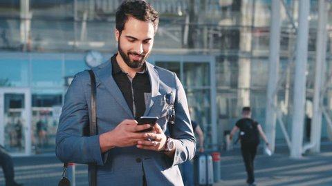Happy bearded man of Eastern appearance going out of the shopping center, joyfully looking around and using his phone, texting back in bright sunlight. Positive mood, business trip.