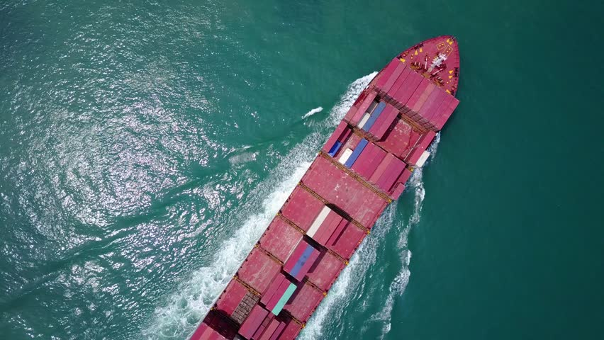 Short top-down aerial clip of large container ship sailing channel. Beautiful turquoise water, shimmering under sunlight, glisten reflection at waves. Vessel loaded with standard intermodal containers