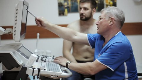 Doctor showing results of ultrasound diagnostic on the screen of sonogram device and advising caucasian male patient. Doctor and patient sitting and talking in ultrasound diagnostic room.