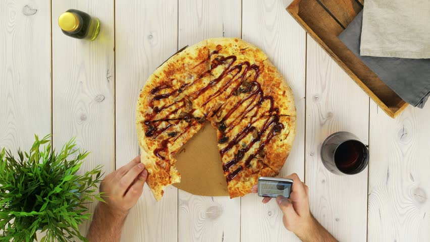 Top view of man s hands. He is eating pizza and swiping his smartphone screen. There is a fuzzy drink on the wooden table. Locked down real time close up shot