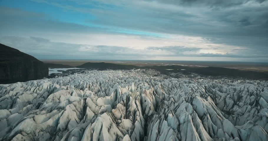Scenic aerial view of the ice valley in Iceland national park. Drone flying over the white glacier Vatnajokull.