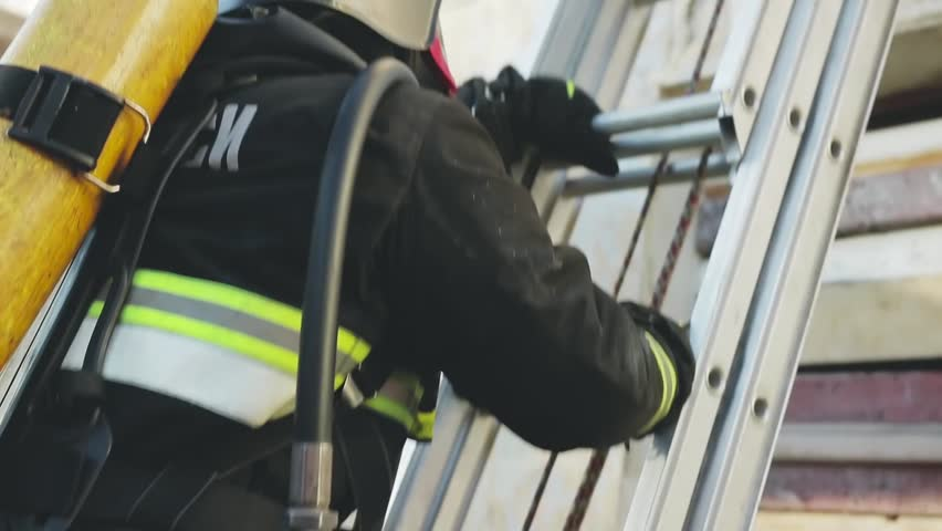 the firefighter climbs the stairs to the window from which smoke