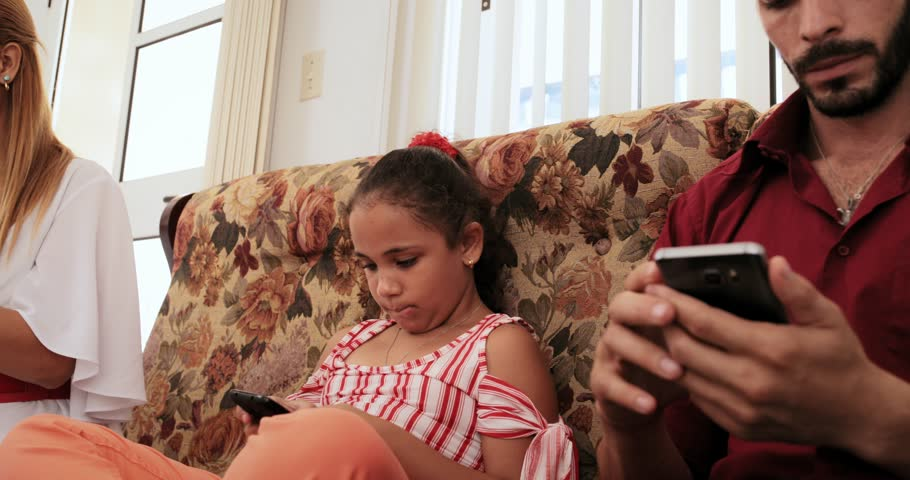 Angry daughter explaining mother and father how to use a cell phone.  Hispanic mom, dad and child with smartphone. Young man, woman, girl and  internet, ...