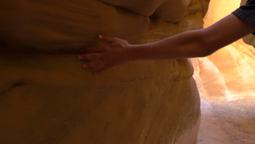 Glide camera close-up of teenage boy's hands sliding along red-rock walls in Bull Valley Gorge slot canyon in the Grand Staircase Escalante National Monument in southern Utah.