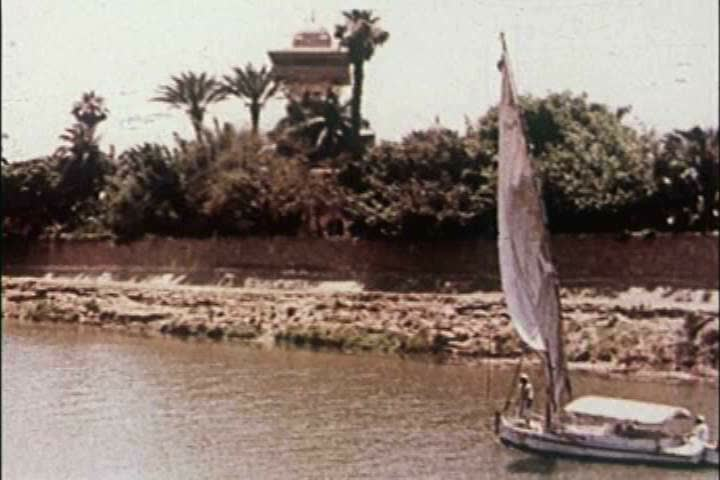 1950s: A boat sails along the Nile River and views of the Pyramids and ancient monoliths are seen in 1959.