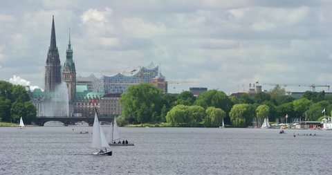 Beautiful view of city hall, Elbphilharmonie and Lombard bridge in Hamburg with sailboats in front