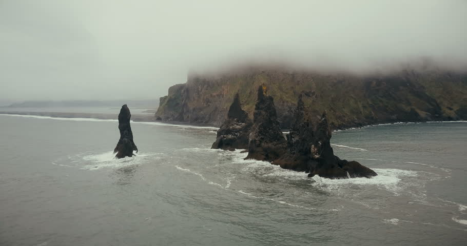 Copter turning around the troll toes cliffs on the sea in Iceland. Beautiful black volcanic beach and mountain in fog.
