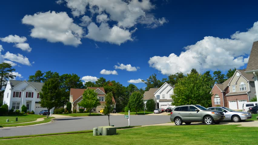 Time lapse of idyllic suburbs with homes on a cul de sac and rolling cumulus clouds on a sunny day timelapse