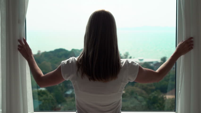 Young woman in white t-shirt opening curtains and looking out of window enjoying the sea view 50 fps. #28046359