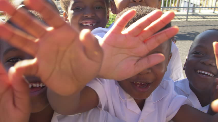 Young school kids in playground waving to camera, close up