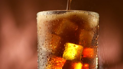 Pouring Cola with ice cubes Cola drink with Ice and bubbles and water drops on glass. Soda closeup. Brown background. Rotation Fizzy drink. 4K UHD video footage. Ultra high definition 3840X2160