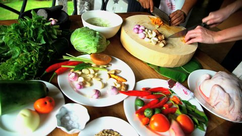 Bali, Indonesia - August 2016: Asian cooking class cutting raw vegetables on wooden chopping board with knives and Balinese Blakas in Indonesia