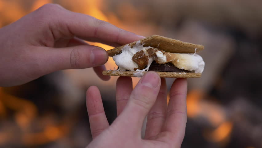 Close up of a woman's hands roasting a marshmallow with a stick on an open fire.