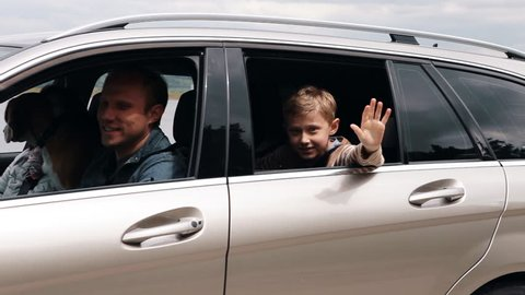 Family goes on vacation and little boy waving into camera