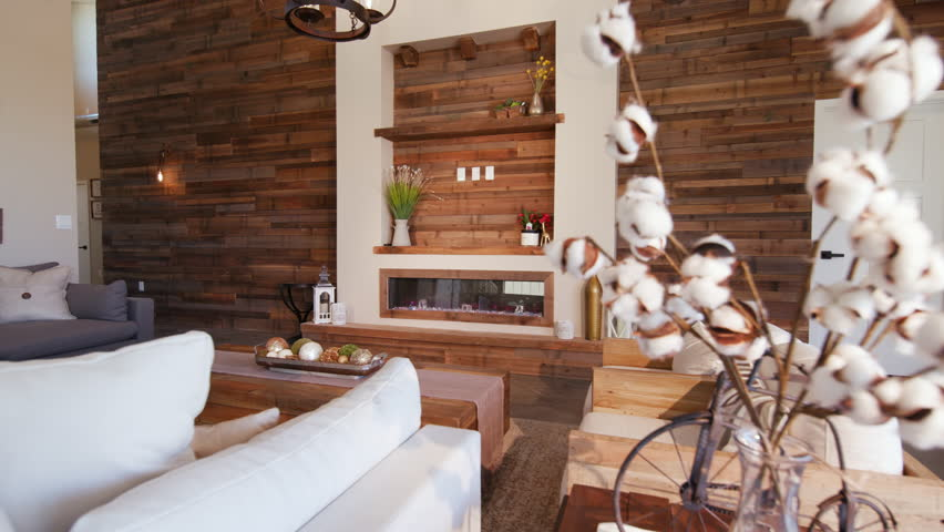 Living Room Reveal Wood Wall from Behind Plant. a large modern rustic industrial living room with a large reclaimed wood wall revealed from behind a plant