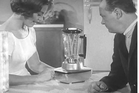 1950s: A television commercial for the Hamilton Beach Cookbook Blender features a happy housewife blending and serving her husband dessert, in 1955.