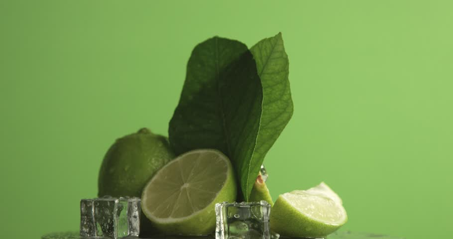 lime turning on it's axis on green background covered by water drops. texture footage