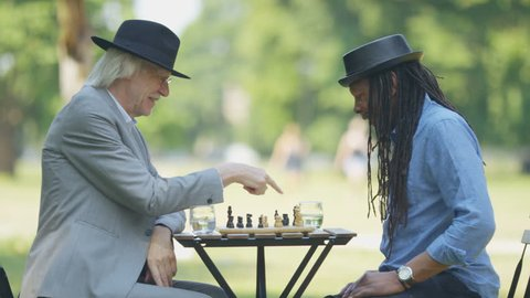 Two old friends in a park shake hands after a game of chess