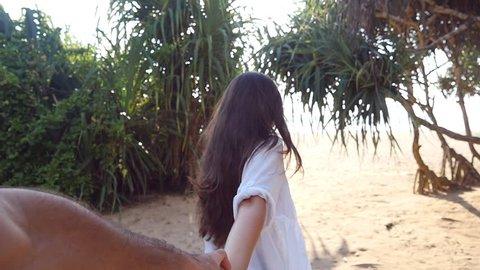 Follow me shot of young woman pull her boyfriend on the sea shore. Girl holding male hand and running on tropical exotic beach to the ocean. Summer vacation or holiday. Point of view. POV Slow motion