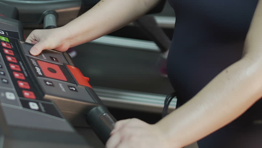 Girl with extra weight adding speed, exercising on treadmill, physical activity