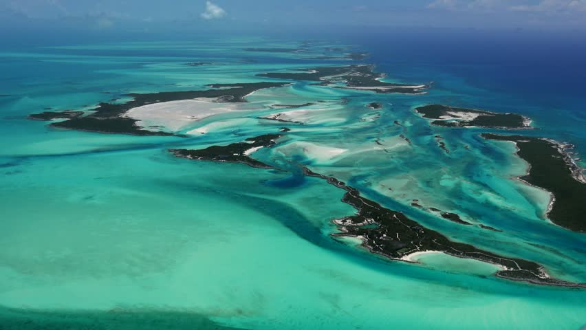 Exumas Bahamas Island Chain, beautiful afternoon AERIALS of colorful water and sand patterns create circle of islands.