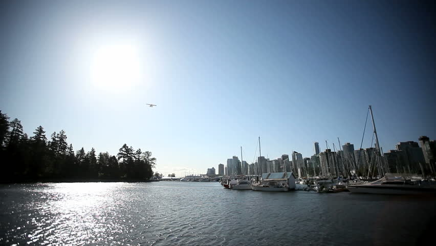 Waterplane flying through the sun over the Vancouver False Creek Marina near Stanley Park