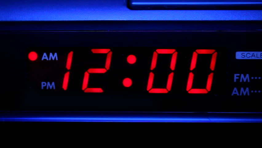 Closeup video of clock radio with blinking red 12:00