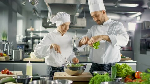 Male and Female Famous Chefs Team Prepare Salad for Their Five Star Restaurant. They Work on a Big Restaurant Stainless Steel Professional Kitchen.  Shot on RED EPIC-W 8K Helium Cinema Camera.